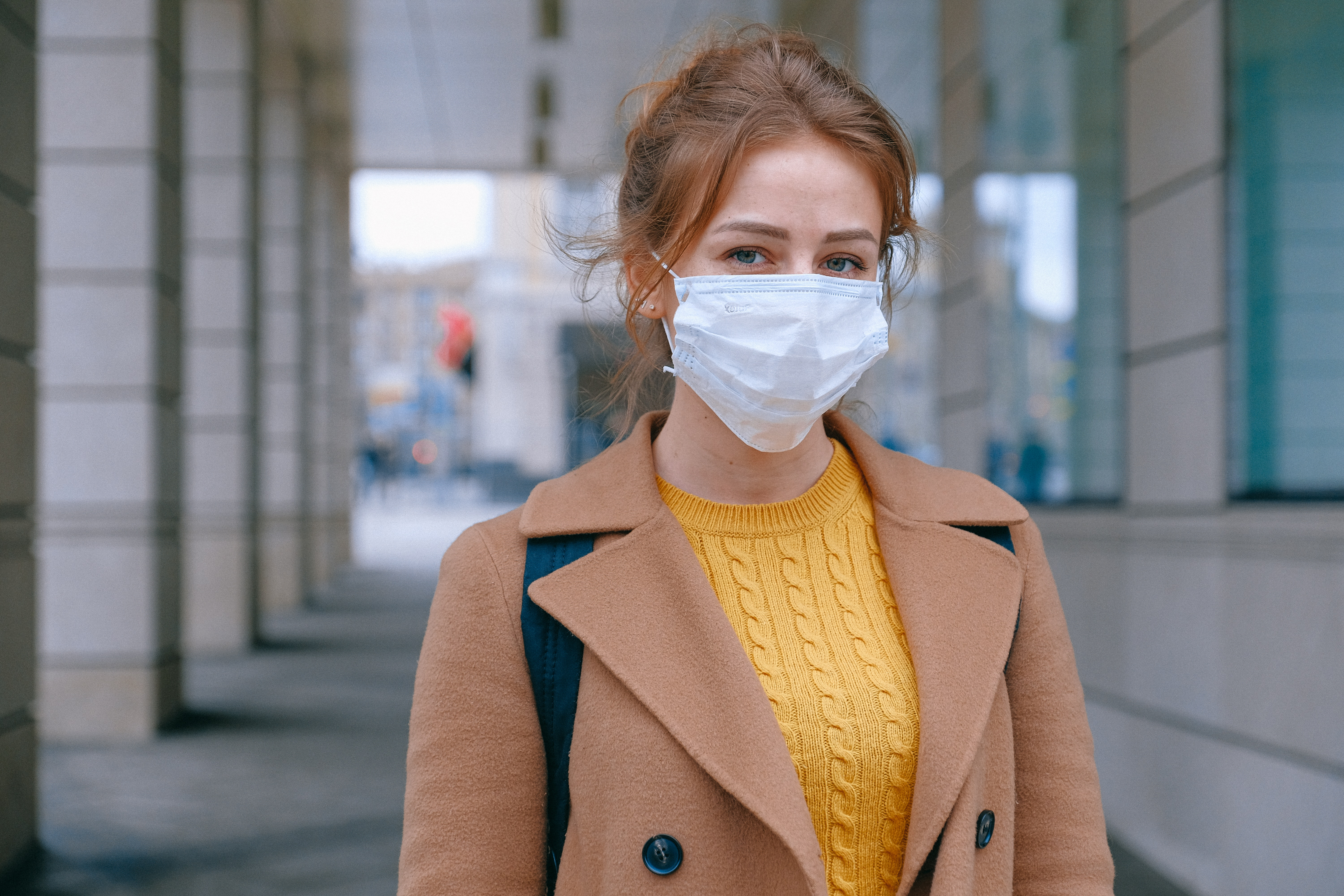 A woman in front of a bank or credit union wearing mask because of Covid-19